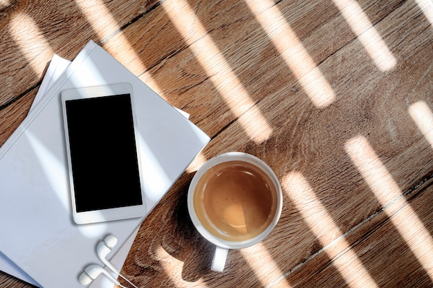 Top view cup of coffee and smartphone with blank screen on white book, copy space.