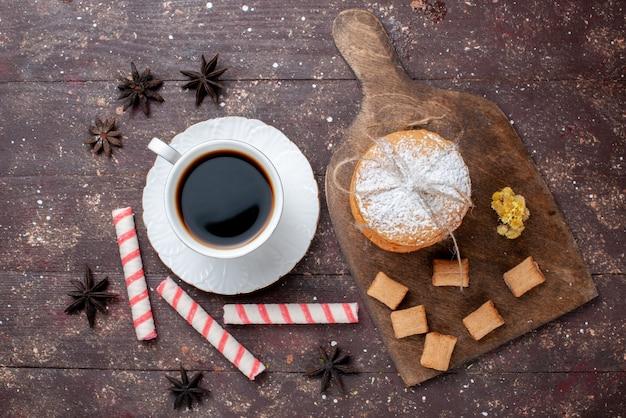 Vista dall'alto della tazza di caffè forte e calda insieme a biscotti e biscotti torta sulla scrivania in legno marrone, frutta cuocere torta al caffè dolce