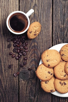 Top view of cup of coffee and tasty chocolate cookies