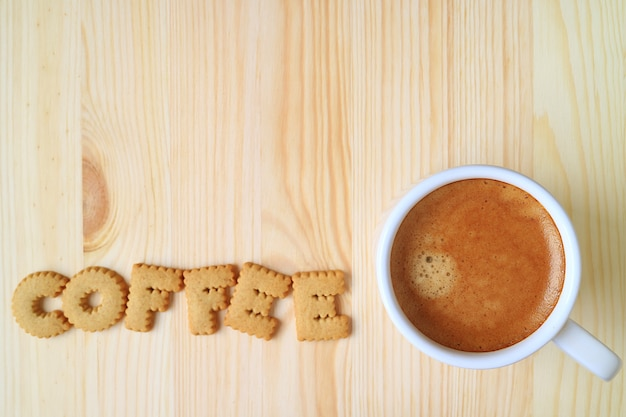 Top view of a cup of coffee with alphabet shaped biscuits spelling the word coffee on wood