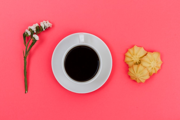 Top view cup of coffee with biscuits and flower