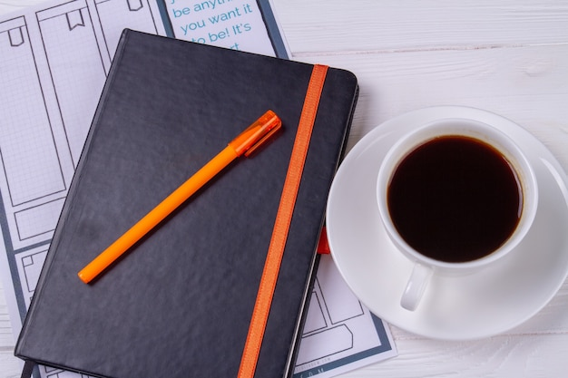 Top view cup of coffee with book and pen.