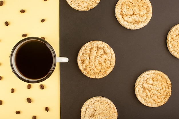 A top view cup of coffee with brown coffee seeds and round crackers