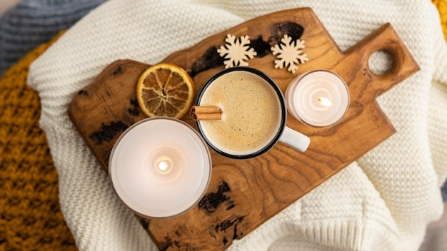 Top view of cup of coffee with candle and dried citrus