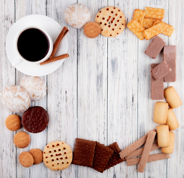 Top view cup of coffee with chocolate cookie crunchy waffles vanilla cookies cinnamon crackers cookies with jam on wooden background