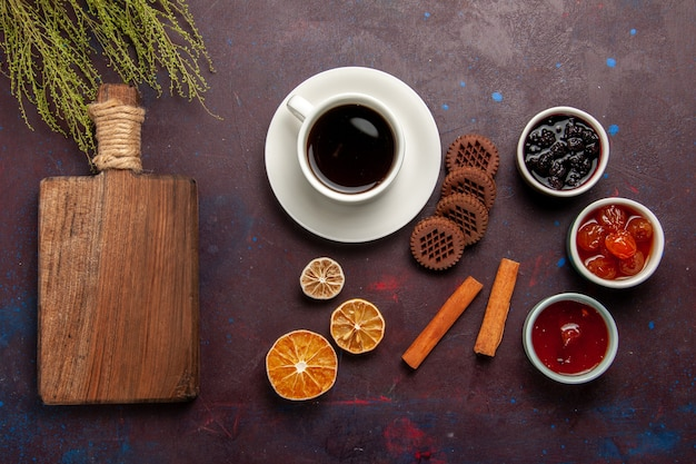 Top view cup of coffee with chocolate cookies and fruit jams on dark background sweet fruit cookie biscuit sweet