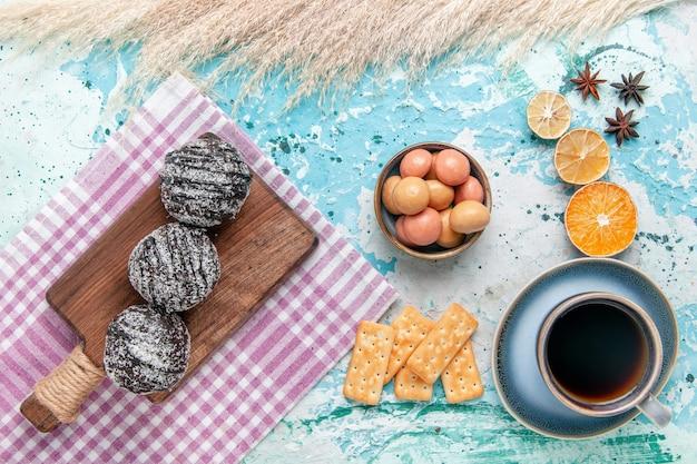 Vista dall'alto la tazza di caffè con torte di glassa al cioccolato e cracker sulla torta azzurra da scrivania cuocere il biscotto di torta di zucchero dolce