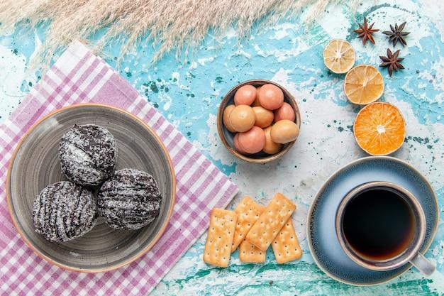Vista dall'alto tazza di caffè con torte glassa al cioccolato e cracker sulla superficie blu chiaro torta cuocere il biscotto torta di zucchero dolce