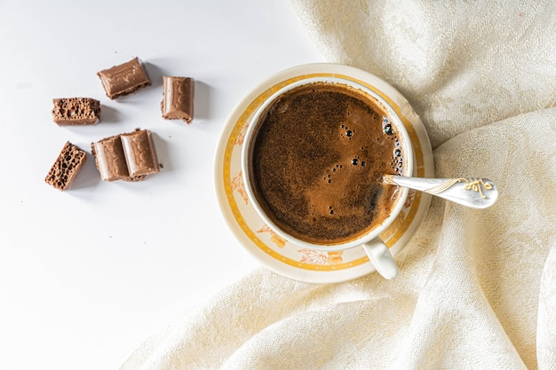 Top view of cup of coffee with chocolate on a light white table and beige napkin