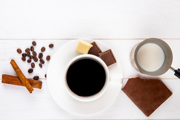 Top view of a cup of coffee with cinnamon sticks chocolate bar and coffee beans scattered on white wooden background