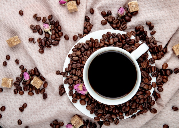 Top view of a cup of coffee with coffee beans brown sugar cubes and tea rose buds