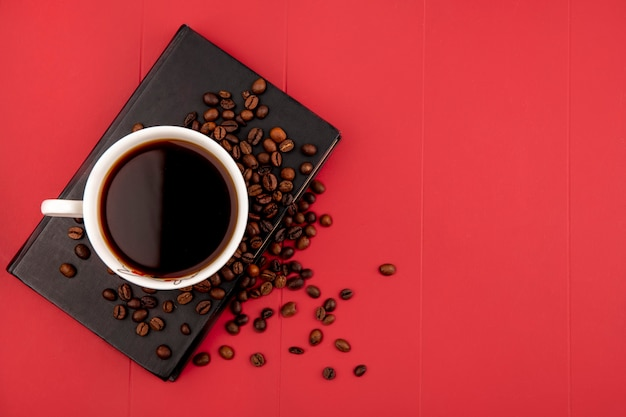 Top view of a cup of coffee with coffee beans on a red background with copy space