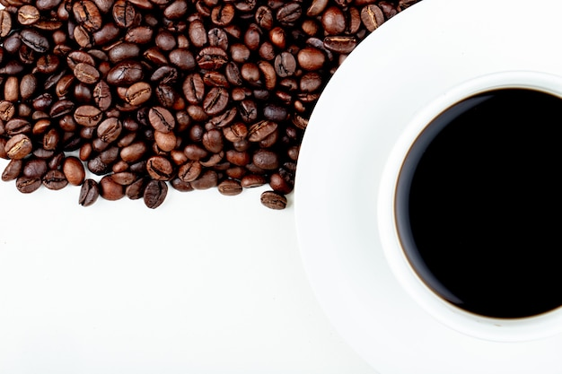 Top view of a cup of coffee with coffee beans on white background with copy space