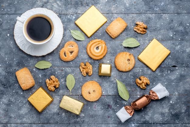 Vista dall'alto della tazza di caffè con biscotti noci sulla scrivania grigia, biscotto biscotto zucchero dolce