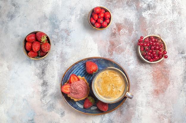 Vista dall'alto tazza di caffè con torta cremosa e frutta sulla torta biscotto dolce tavolo luminoso