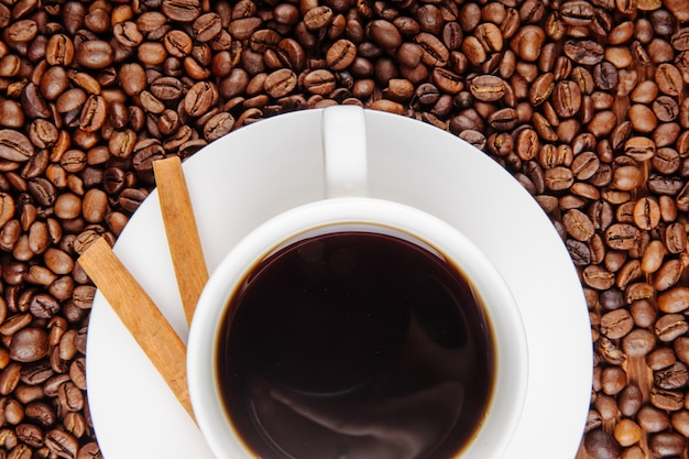 Top view of a cup of coffee with crispy sticks on coffee beans background