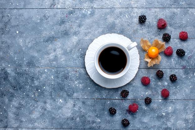 Vista dall'alto della tazza di caffè con diversi frutti di bosco su grigio, colore della bevanda del caffè ai frutti di bosco