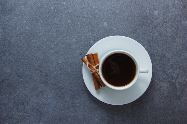 Top view a cup of coffee with dry cinnamon on gray surface. horizontal space for text