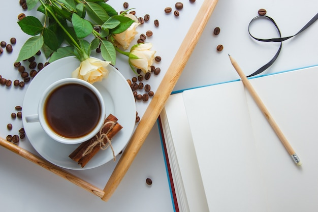 Top view a cup of coffee with flowers, coffee beans, pencil and notebook on white surface horizontal