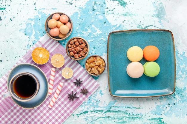 Vista dall'alto tazza di caffè con macarons francesi uvetta e confetture sulla torta da scrivania azzurra cuocere il biscotto con torta di zucchero