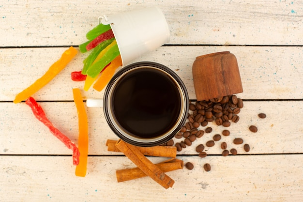 A top view cup of coffee with fresh brown coffee seeds and colorful marmalade