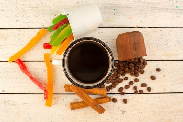 Una tazza di caffè vista dall'alto con semi di caffè marroni freschi e marmellata colorata