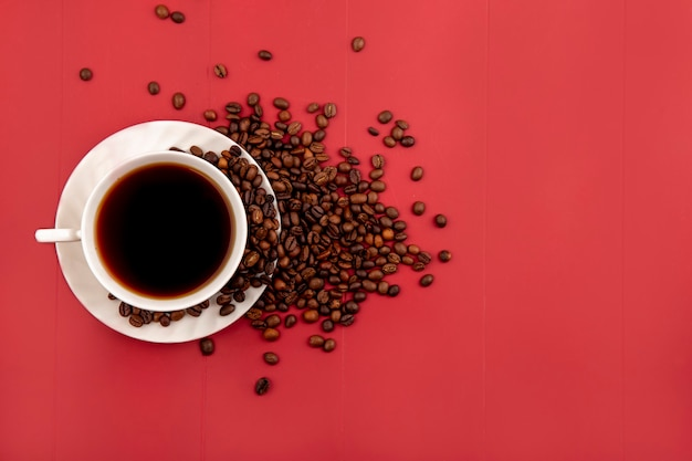 Top view of a cup of coffee with fresh roasted coffee beans isolated on a red background with copy space