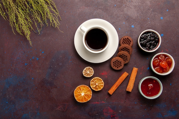 Top view cup of coffee with jams and chocolate cookies on dark background fruit jam marmalade sweet