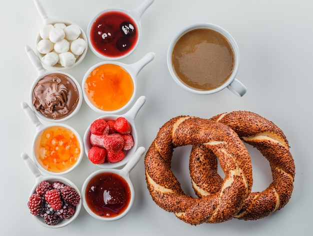 Top view a cup of coffee with jams, raspberry, sugar, chocolate in cups and turkish bagel on white surface