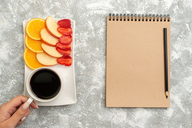 Top view cup of coffee with notepad sliced apples oranges and strawberries on white background fruit ripe fresh mellow