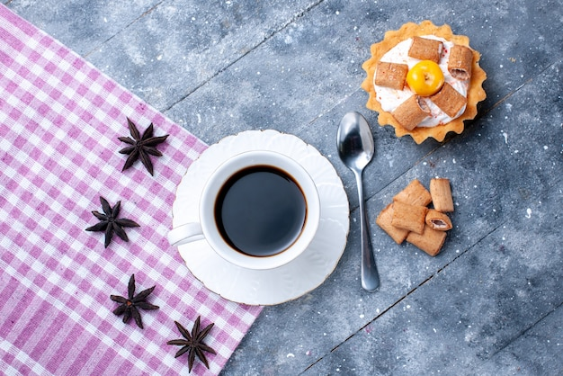 Vista dall'alto della tazza di caffè con biscotti a forma di cuscino e torta cremosa su pasta dolce brillante, biscotto al caffè