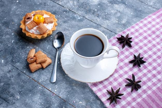 Vista dall'alto della tazza di caffè con biscotti a forma di cuscino e torta cremosa su pasta dolce brillante, biscotti al caffè