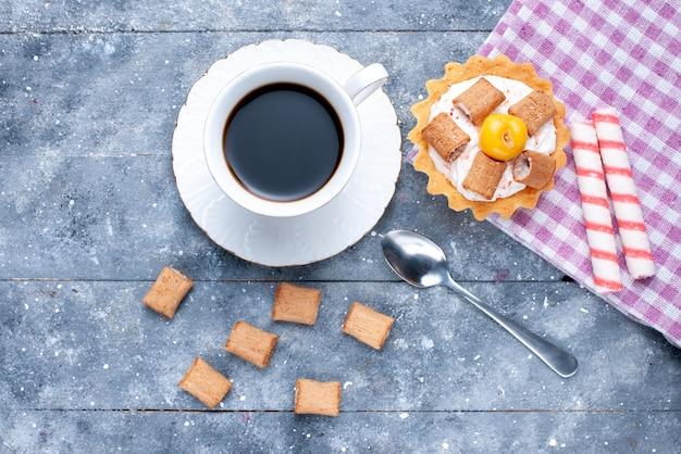 Vista dall'alto della tazza di caffè con biscotti a forma di cuscino e torta cremosa su grigio, pasta dolce biscotto al caffè