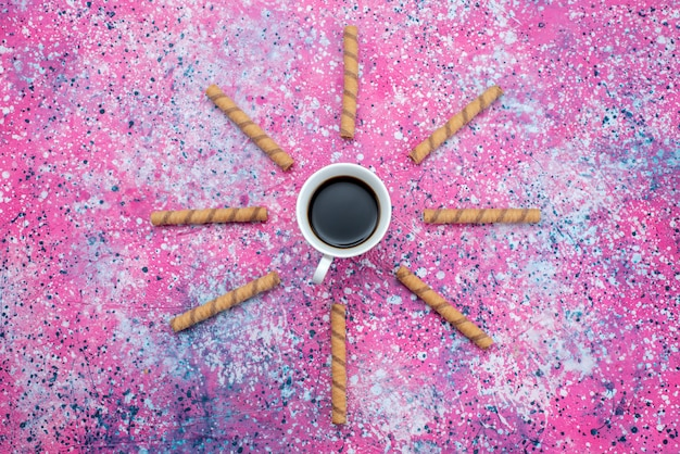 Top view cup of coffee with pipe formed cookies on the colored background sweet cracker biscuit color