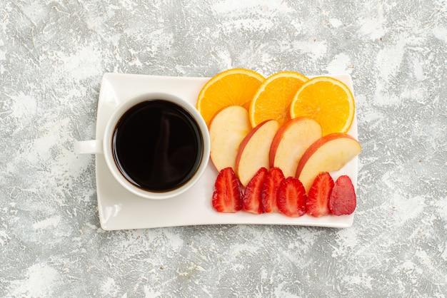 Vista dall'alto tazza di caffè con mele a fette arance e fragole su sfondo bianco frutta matura fresca pastosa