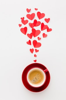 Top view of cup of coffee with valentines day paper heart shapes