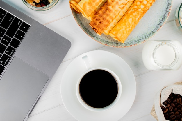 Top view of a cup of coffee with wafer rolls and laptop on white wooden background