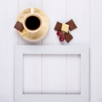 Top view of a cup of coffee with white and dark chocolate and an empty picture frame on white wooden background with copy space