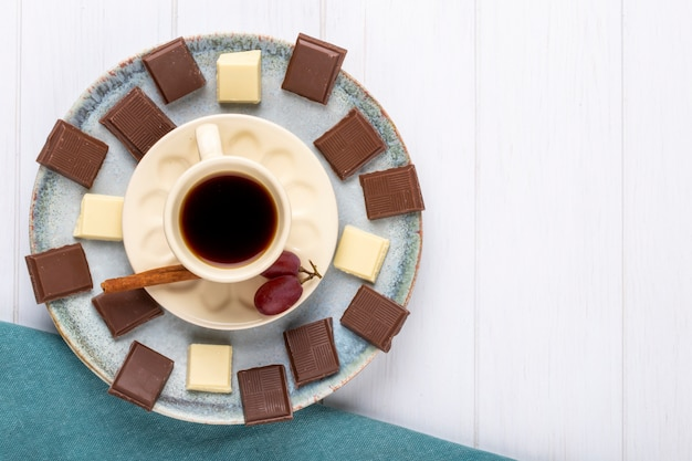 Top view of a cup of coffee with white and dark chocolate on white wooden background with copy space