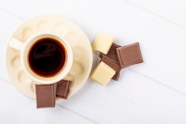 Top view of a cup of coffee with white and dark chocolate on white wooden background