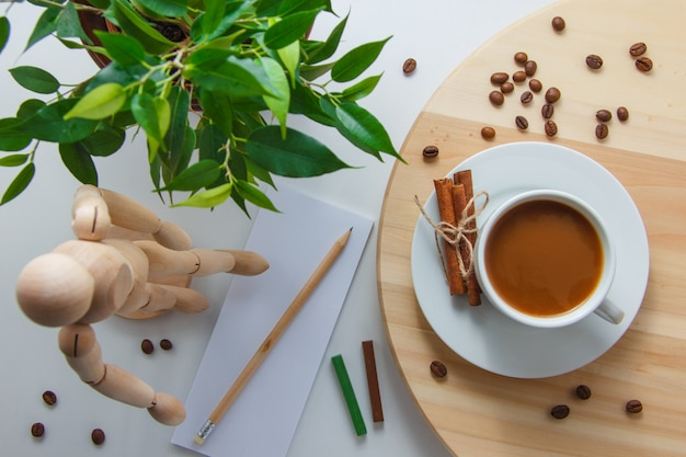 Top view a cup of coffee with wooden robot, plant, coffee beans, dry cinnamon, paper and pencil on platform and white surface. horizontal