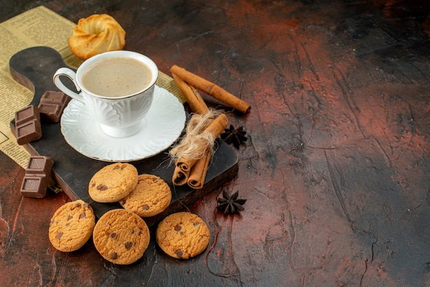 Top view of cup of coffee on wooden cutting board cookies cinnamon limes chocolate bars on the right side on dark surface