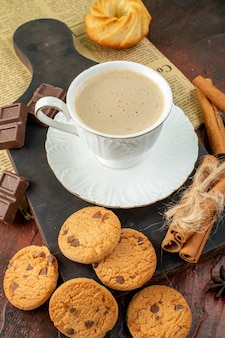 Top view of cup of coffee on wooden cutting board on an old newspaper cookies cinnamon limes chocolate bars on dark background
