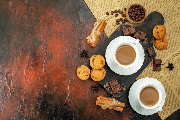 Top view of cup of coffee on wooden cutting board on an old newspaper cookies cinnamon limes chocolate bars on the left side on dark background