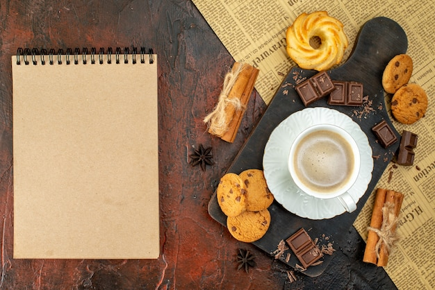 Top view of cup of coffee on wooden cutting board on an old newspaper cookies cinnamon limes chocolate bars notebook on dark surface
