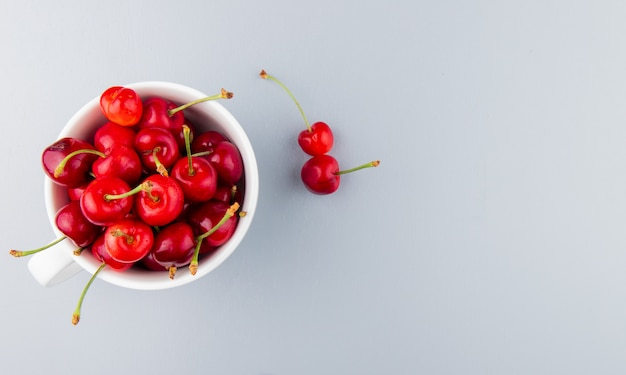 Top view of cup full of red cherries on left side and white surface with copy space