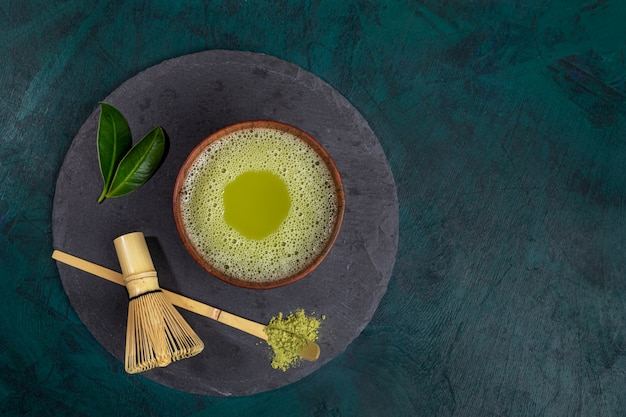 Top view cup of green matcha tea on shale serving board on emerald background with copy space.