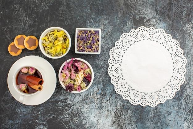 Vista dall'alto di una tazza di tisana con biscotti e fiori secchi e pizzo bianco su sfondo grigio