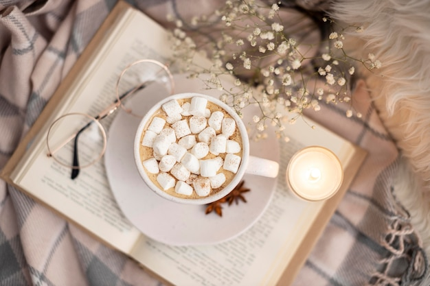 Top view of cup of hot cocoa with marshmallows on book with glasses and candle