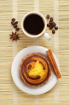 Top view on cup of hot coffee and plate with delicious cupcake